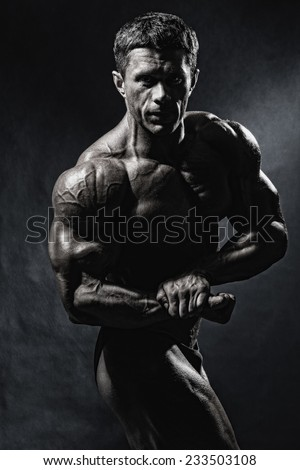 Handsome muscular bodybuilder posing over blue background. Monochrome image - stock photo