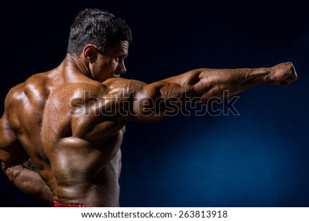Handsome muscular bodybuilder posing over blue background. Trained athlete's body