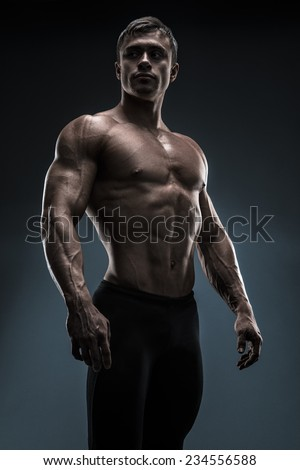 Handsome muscular bodybuilder preparing for fitness training. Studio shot on black background. - stock photo