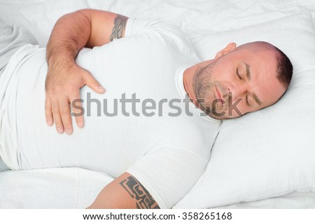 Handsome muscular bodybuilder with tribal tattoos sleeping in bed.