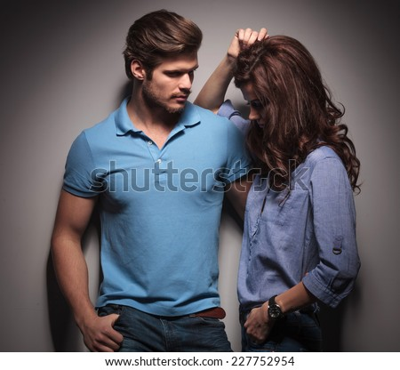Handsome muscular fashion man looking at his lover, holding her while she is leaning on him, looking down. - stock photo