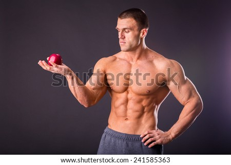 Handsome muscular guy posing on a dark background, holding a juicy, ripe apple. Concept of healthy food.