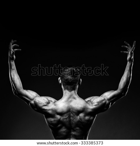 Handsome muscular male bodybuilder posing and turned his back