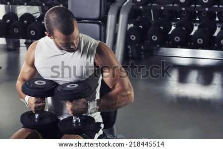 Handsome Muscular Male Model Posing With Dumbbells  - stock photo