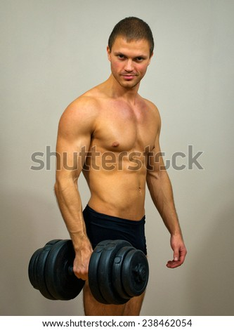 Handsome muscular male model with dumbbell.