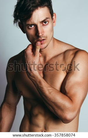 Handsome muscular male model with intense glance posing over grey background. Studio shot