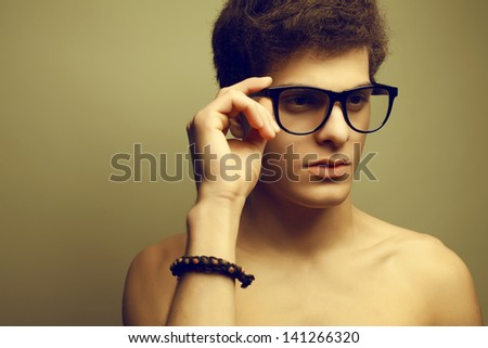 Handsome muscular male model with nice body wearing leather bracelet, trendy glasses and posing over light-gray background. Hipster & vintage (retro) style. Close up. Copy-space. Studio portrait