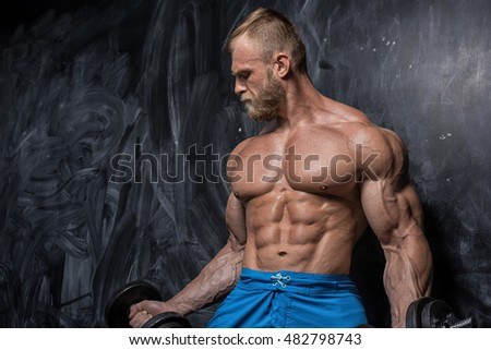 Handsome muscular man bodybuilder posing in the studio on a darck background