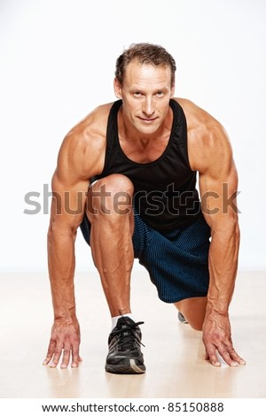 Handsome muscular man doing fitness exercise. - stock photo