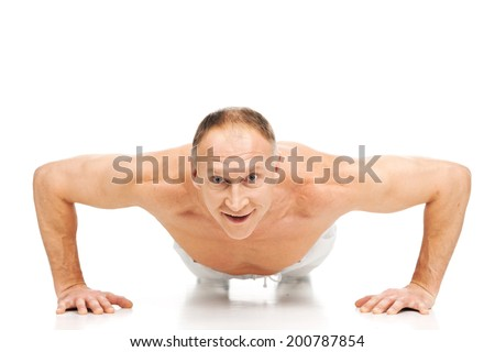 handsome muscular man doing push-ups. aged male workout on white background - stock photo