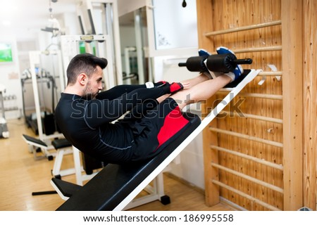 Handsome muscular man doing sit-ups on a incline bench at fitness center and gym - stock photo