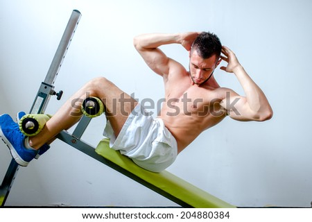 Handsome muscular man doing sit-ups on a incline bench at fitness center or gym - stock photo