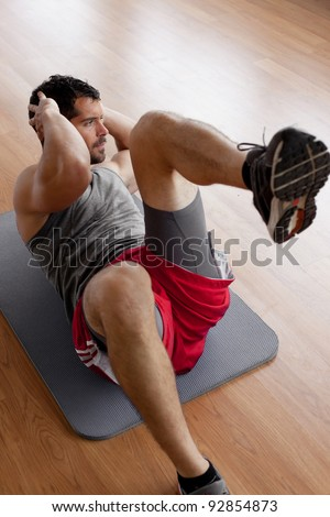 Handsome muscular man doing sit-ups on a wooden floor. - stock photo