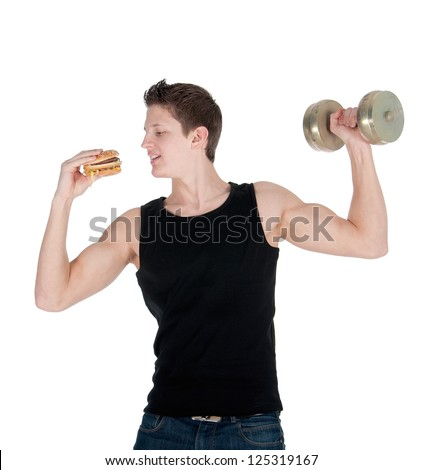 Handsome muscular man eats a hamburger while doing bicep curls.