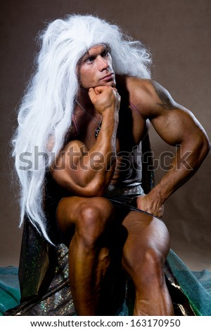 Handsome muscular man in a pose of a thinker. The athlete with long white hair. - stock photo