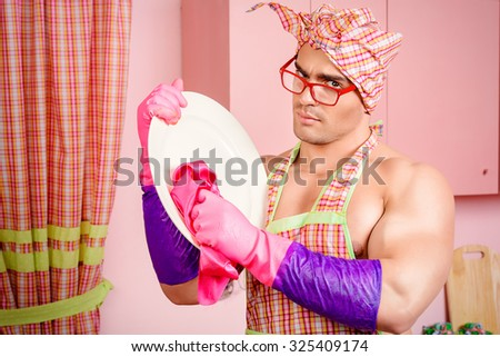 Handsome muscular man in an apron washing the dishes the pink kitchen. Love, family concept. Valentine's day.