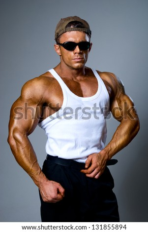 Handsome muscular man in dark glasses and a white shirt - stock photo