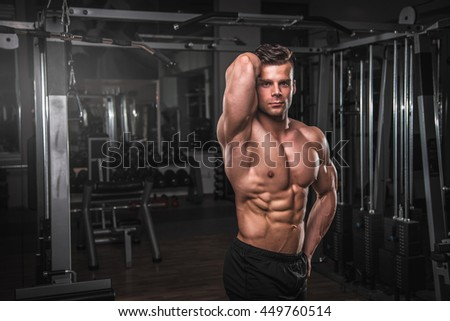 Handsome muscular man in gym. - stock photo