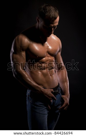 Handsome, muscular man in jeans, with in water-drops
