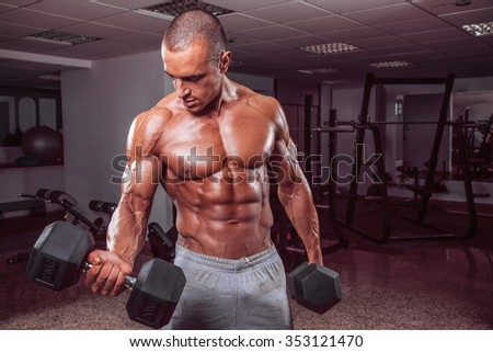 Handsome muscular man in the gym. - stock photo