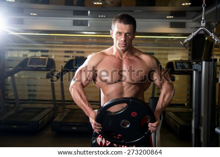 Handsome muscular man in the gym. Bodybuilder with the disc. Muscle training, fitness - stock photo