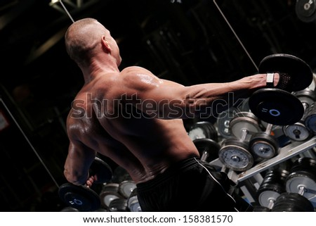 Handsome muscular man is working out and posing at a gym - stock photo