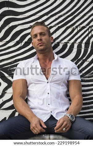 Handsome muscular man leaning against graffiti wall with zebra pattern, looking at camera - stock photo