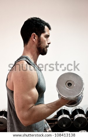 Handsome muscular man lifting weights. - stock photo