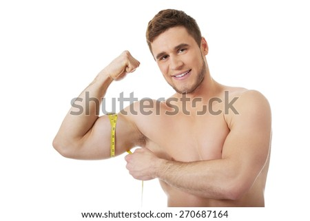 Handsome muscular man measuring his biceps. - stock photo