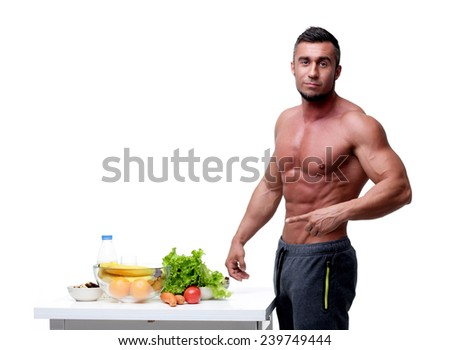 Handsome muscular man pointing at healthy food - stock photo