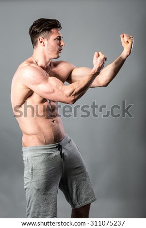 Handsome muscular man posing against a dark background