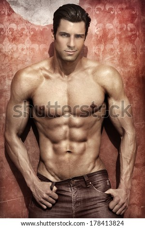 Handsome muscular man posing against vibrant elegant background - stock photo