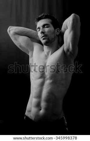 Handsome muscular man posing in the dark  - stock photo