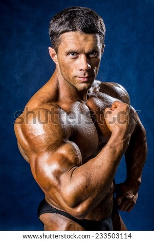 Handsome muscular man posing over blue background.  - stock photo