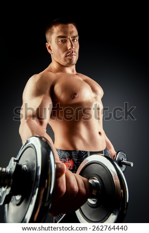 Handsome muscular man posing with dumbbells over black background. Bodybuilding. Professional sports. - stock photo