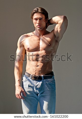 Handsome muscular man shirtless wearing jeans with hand behind his head - stock photo