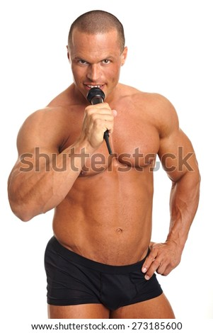 Handsome muscular man sings into microphone