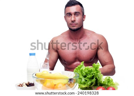 Handsome muscular man sitting at the table with healthy food - stock photo