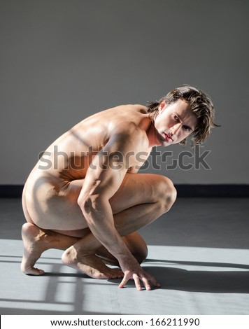 Handsome, muscular man totally naked, kneeling on the floor in studio shot - stock photo