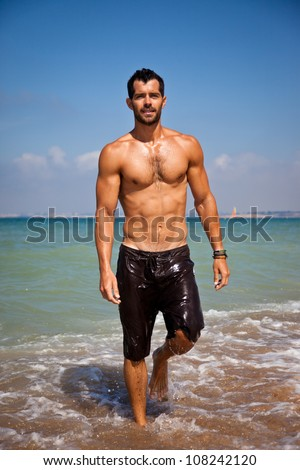 Handsome muscular man walking out of the water on a turquoise water beach. - stock photo