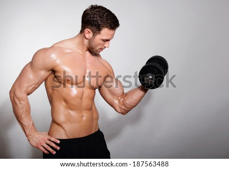 Handsome, muscular man with dumbbell - stock photo