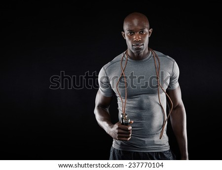 Handsome muscular man with jumping rope on black background. Fit african model with lots of copy space. - stock photo