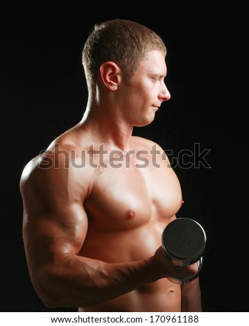 Handsome muscular man working out with dumbbells - stock photo