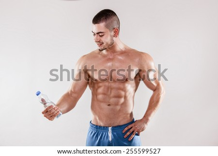 Handsome muscular men holding a bottle of water in his hand.