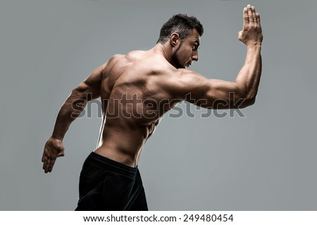 Handsome muscular mna posing over gray background - stock photo