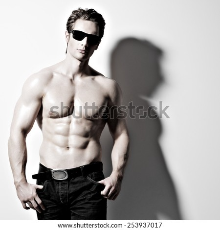 Handsome muscular sexy man in glasses posing at studio as fashion model on a white background with contrast shadows.