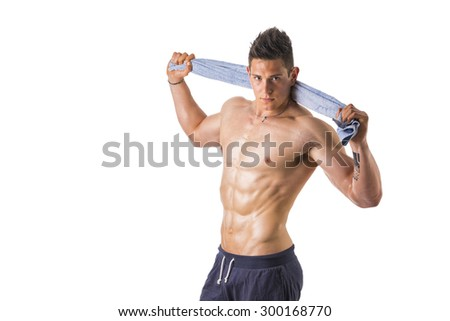 Handsome muscular shirtless athletic young man holding towel, isolated on white background - stock photo