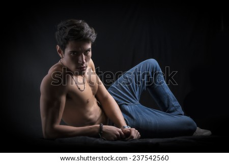 Handsome muscular shirtless young man laying down on the floor confident, profile view, looking at camera