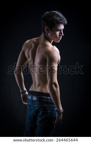Handsome muscular shirtless young man standing confident, seen from the back - stock photo