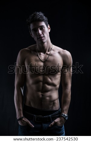 Handsome muscular shirtless young man standing confident with hands in his pockets